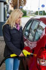 Frau beim tanken auf Tankstelle
