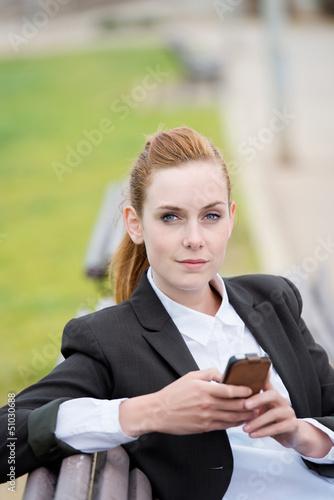 frau im park mit smartphone