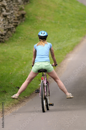 Female cyclist riding with her legs outstretched