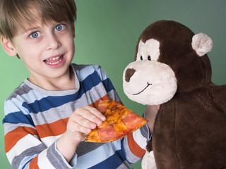 Cute boy feeding his monkey doll with pizza