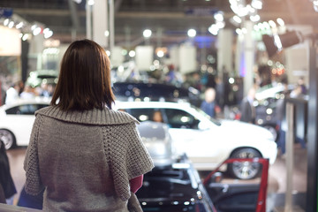 girl watching a car exhibition