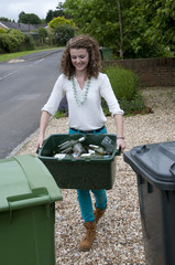 Woman putting glass recyclables out for collection