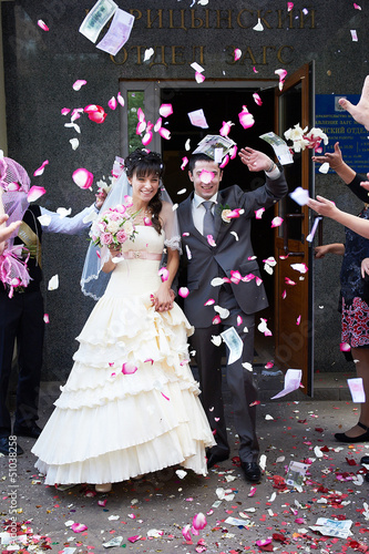 Happy newlyweds and flying petals