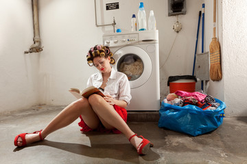 A housewife reading a book in the laundry room