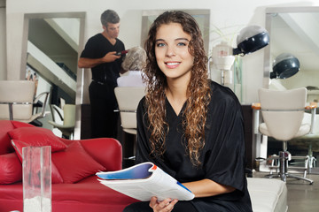Client Holding Magazine With Hairdresser Working At Salon