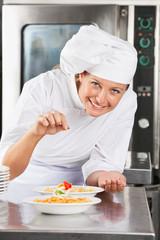 Happy Chef Adding Spices To Dish