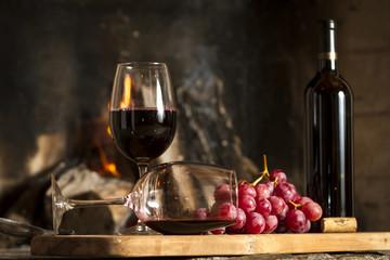 Copas de vino tinto, botella uvas y corcho.