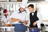 Waiter And Chef Using Digital Tablet In Kitchen