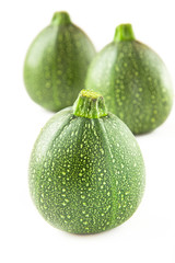 Isolated round courgette on white