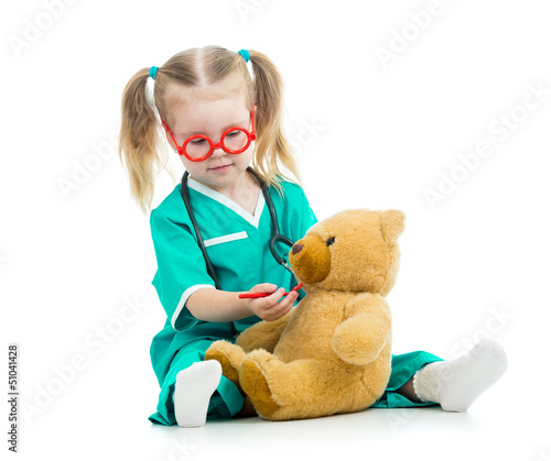 Fototapeta child girl dressed as doctor playing with toy
