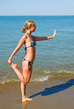 Slender girl doing yoga on the beach
