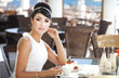 Woman in cafe restaurant with retro hairstyle and makeup