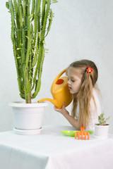 Девочка поливает из лейки кактусы