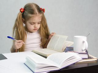 Девочка листает книгу и пишет на листе бумаги сидя за столом