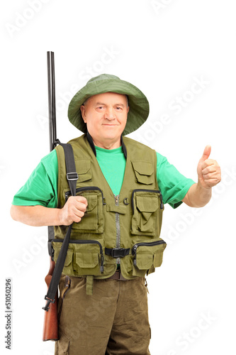 A mature hunter holding a rifle and giving a thumb up