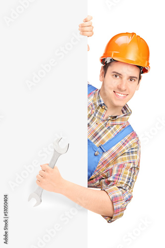 Young construction worker with helmet posing behind a panel and