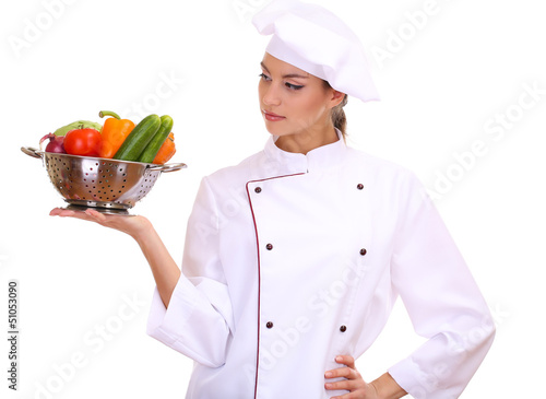Portrait of young woman chef with vegetables isolated on white