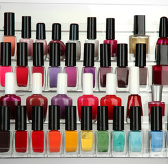 Bright nail polishes on shelf on grey background