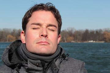 Mann relaxt im Winter im Sonnenschein am See