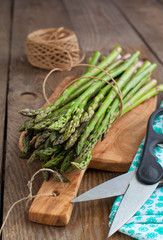Fresh green asparagus sprouts on wooden table