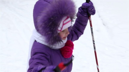 little girl is skiing in the forest.