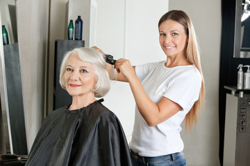 Hairdresser Ironing Woman's Hair