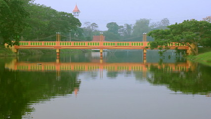 yellow bridge with reflections on  lake