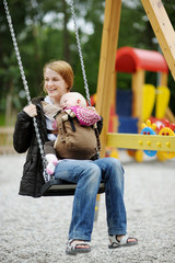 Young mother on a swing with baby
