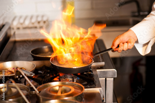 Tuinposter Koken Chef cooking in kitchen stove