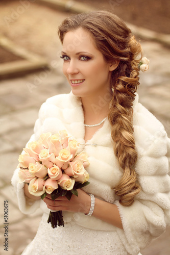 Outdoors portrait of Beautiful bride with bouquet of flowers