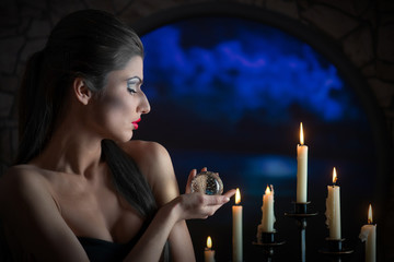 Indoors portrait of a sorceress with glass sphere and candles