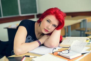 Рыжая девушка делает уроки