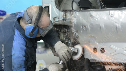 repairman grinding metal body car