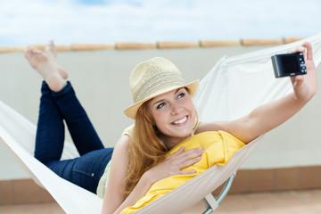 lachende frau fotografiert sich selbst in hängematte