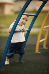 little boy plays on playground