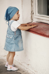 young girl looks to the window