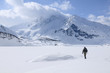 A lone hiker in the cold landscape of Mont Cenis ( France ).