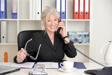 Attraktive ältere Geschäftsfrau bei einem Telefongespräch