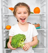 little girl  against a refrigerator