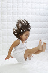 A happy young girl in white dress having fun jumping on bed