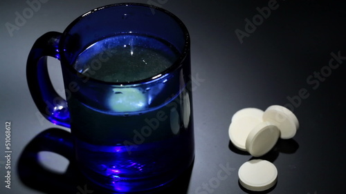 Tablet dissolving in a blue glass of water.