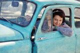 beautiful girl sitting in an old car and smiling with pleasure poster