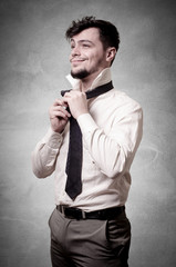 Sexy stylish businessman adjusting tie