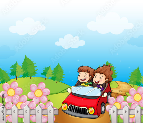A red car with a young girl and boy