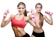 Two beautiful young women doing fitness exercise with dumbbells