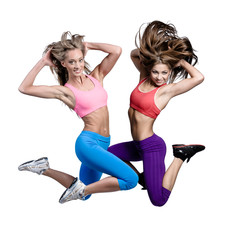 Two beautiful athletic girls jumping over white background