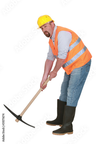 Construction worker with pickaxe on white background