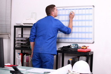Factory worker marking date on calendar