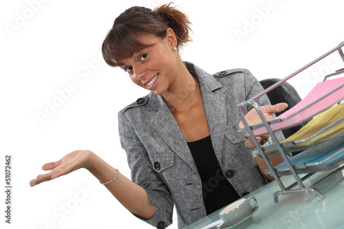 Happy receptionist presenting her work area