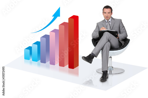 Businessman with an upwards growth chart